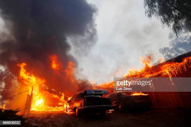 A home and cars are engulfed in flames in the path of the Creek Fire near the intersection of Johanna Avenue and McBroom Street in Shadow Hills on...