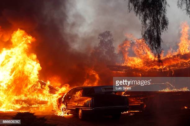 A home and cars in the path of the Creek Fire are engulfed in flames near the intersection of Johanna Avenue and McBroom Street in Shadow Hills on...