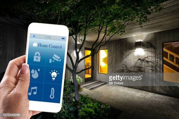 home automation: woman holding smart home app with smart phone in living room of house. concept for home automation - house icon stock pictures, royalty-free photos & images