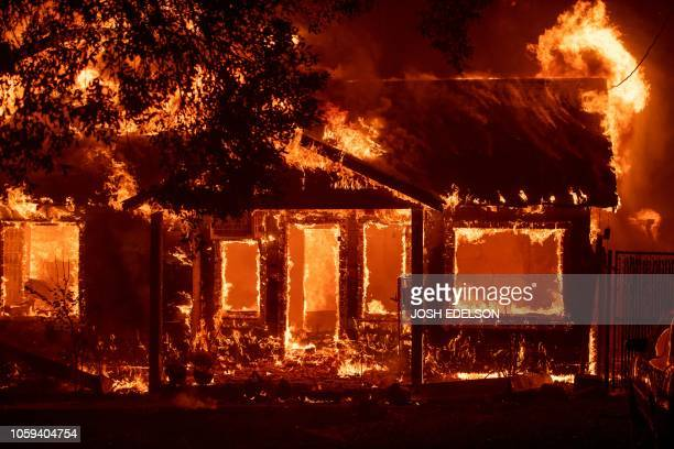 Home burns as the Camp fire tears through Paradise, California on November 8, 2018. - More than 18,000 acres have been scorched in a matter of hours...
