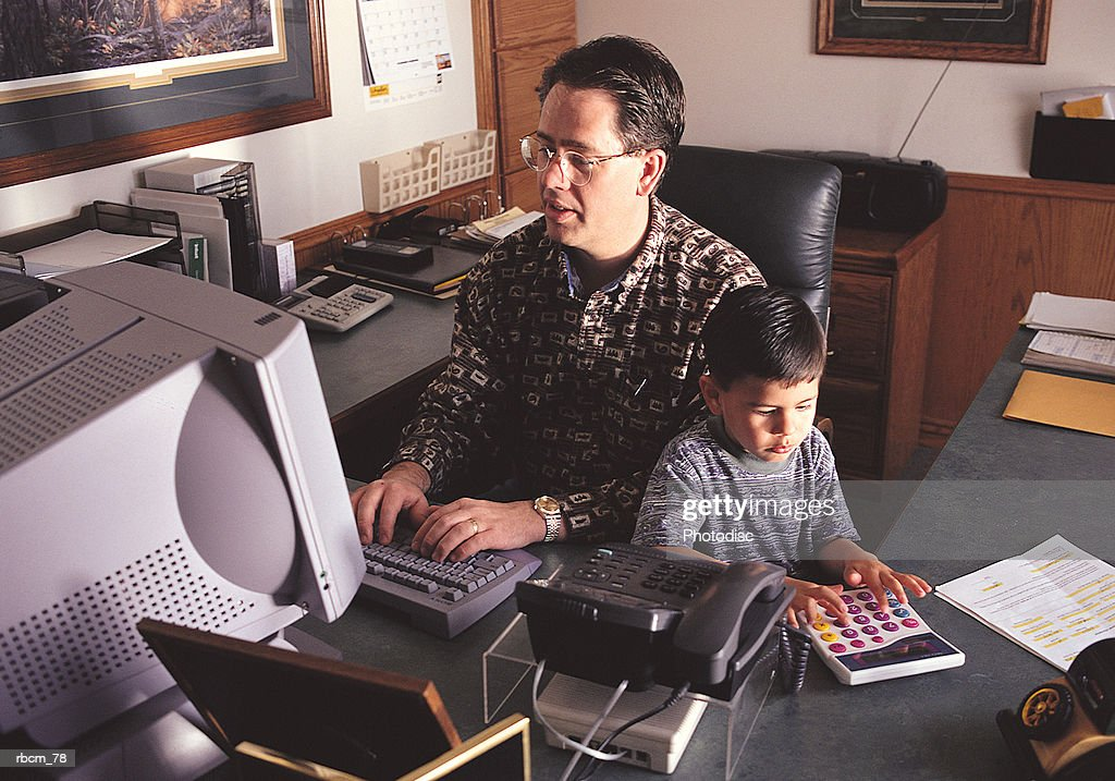 A home businessman and his son share a chair as they work in a home office : Stockfoto