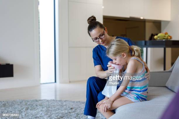 home call nurse using sick bag with child at home - sick bag stock photos and pictures