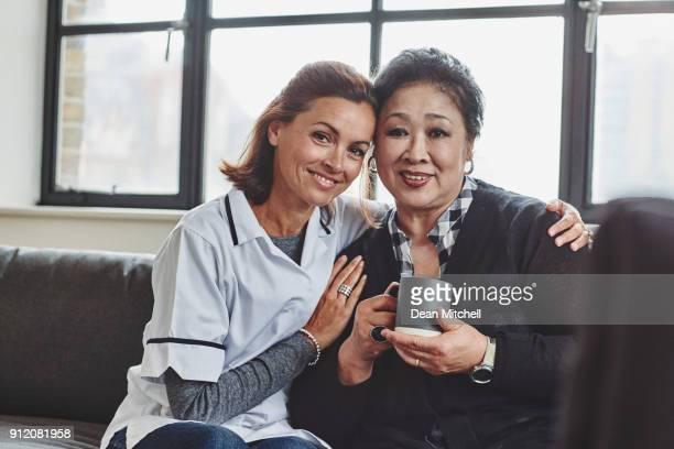 Aide familiale et haute femme siégeant ensemble
