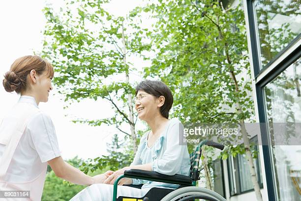 Home caregiver and woman in wheelchair smiling