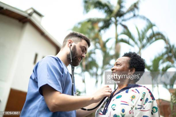home caregiver examining senior woman - latin america stock pictures, royalty-free photos & images