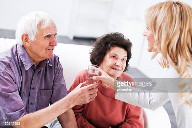 Home caregiver giving a senior couple glass of water.