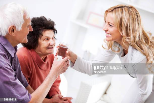 Home caregiver giving a senior man glass of water