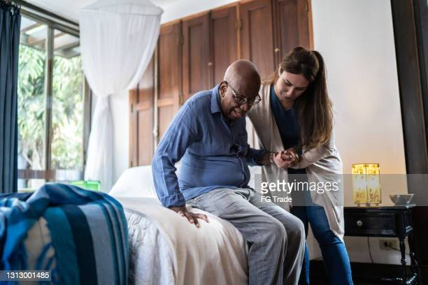home caregiver helping a senior man standing up at home - fragility stock pictures, royalty-free photos & images