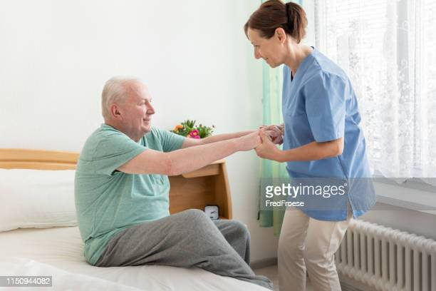 home caregiver helping an elderly man out of bed - carrying stock pictures, royalty-free photos & images