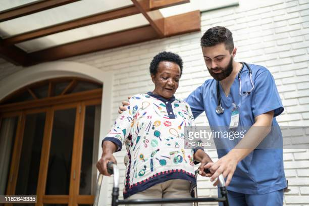 home caregiver helping senior woman to walk - retirement community stock pictures, royalty-free photos & images