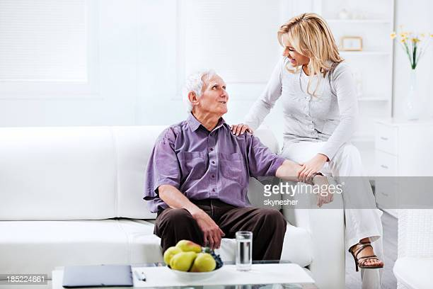 Home caregiver sitting on the sofa with an elderly man
