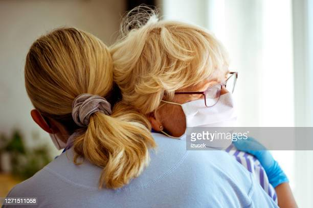 home caregiver supporting senior woman during coronavirus pandemic - embracing stock pictures, royalty-free photos & images