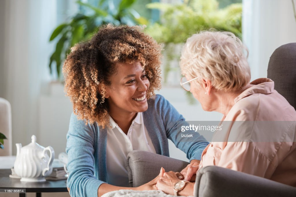 Home caregiver taking care of elderly woman : Stock Photo