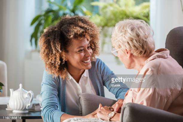 home caregiver taking care of elderly woman - care stock pictures, royalty-free photos & images