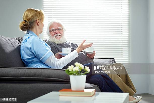 Home caregiver talking with senior man while sitting on sofa