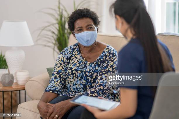 home caregiver visiting with patient wearing masks - fatcamera stock pictures, royalty-free photos & images