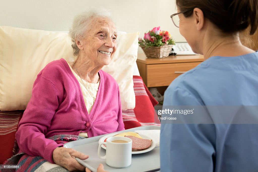 Home caregiver with senior adult woman, serving a meal : Stock Photo