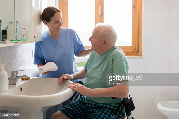 home caregiver with senior man in bathroom - social services stock photos and pictures