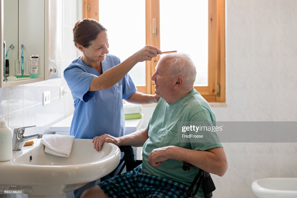 Home Caregiver with senior man in bathroom : Stock Photo
