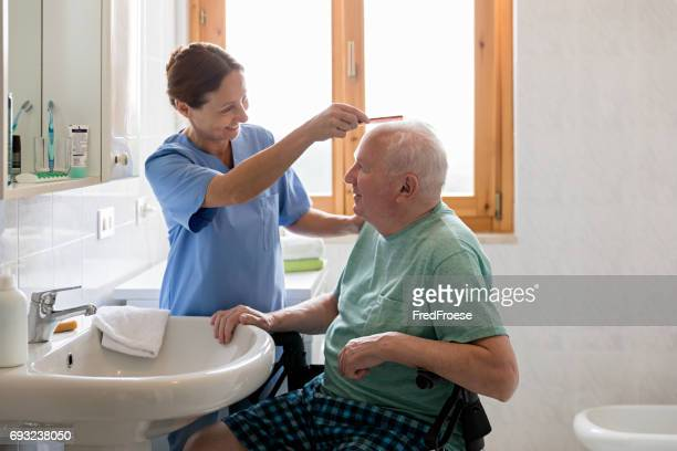 Home Caregiver with senior man in bathroom