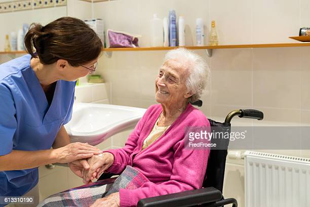 home caregiver with senior woman in bathroom - infermiera foto e immagini stock