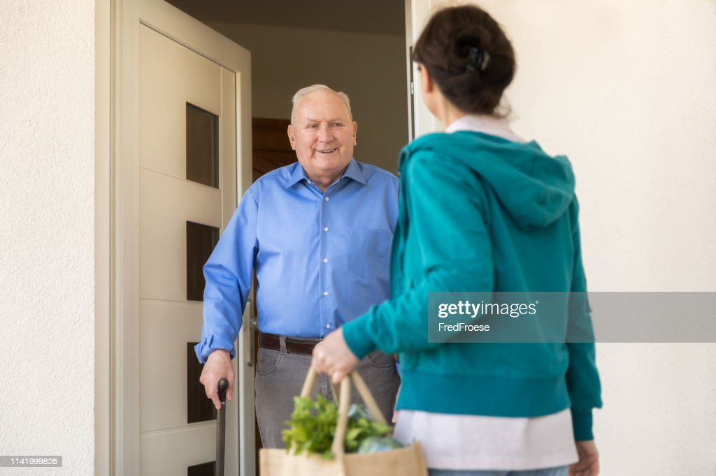 Home caregiver – woman helping senior man : Stock Photo
