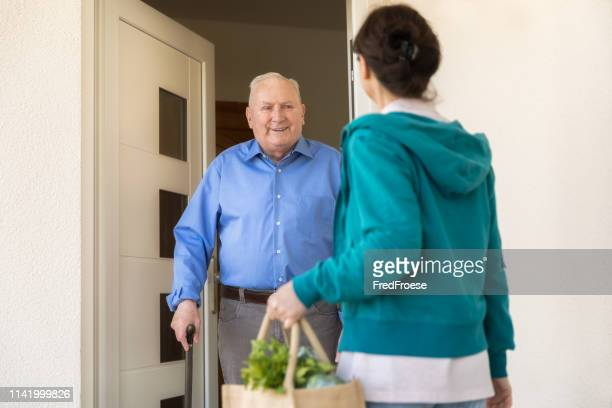 home caregiver – woman helping senior man - assistance stock pictures, royalty-free photos & images