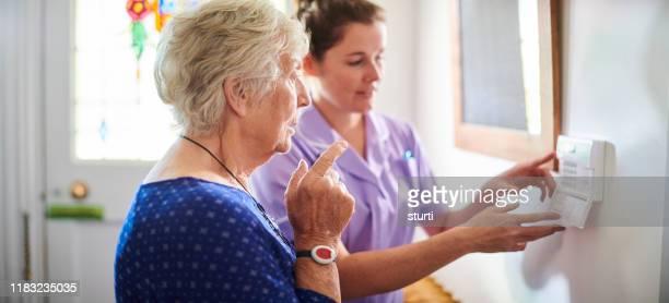 home verzorger toont senior vrouw haar alarm panel - sociale dienst stockfoto's en -beelden