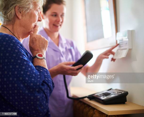 home carer showing senior woman her intercom - bracelet stock pictures, royalty-free photos & images