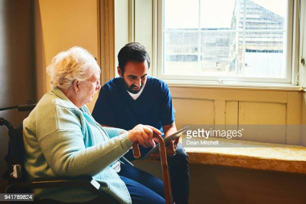 Home carer with elderly woman using digital tablet