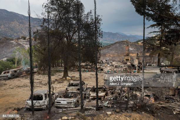 A home cars and property lies in ruins as it was one of three homes and a shed were destroyed in the the La Tuna Canyon fire along Crestline Drive in...