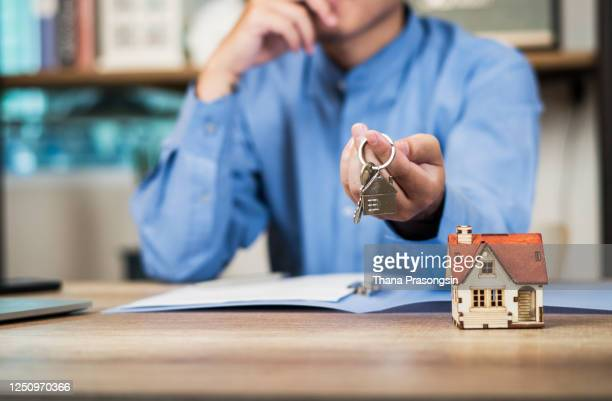 home concept businessmen holding home keys - キーホルダー ストックフォトと画像