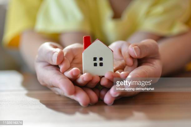 home concept,people, family and home concept - close up of woman and boy holding model house,home insurance - housing difficulties stock pictures, royalty-free photos & images