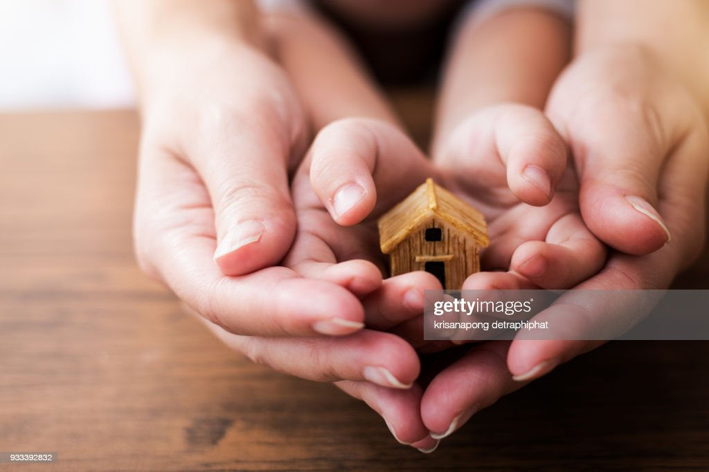 Home concept,people, family and home concept - close up of woman and girl holding model house : Stock Photo