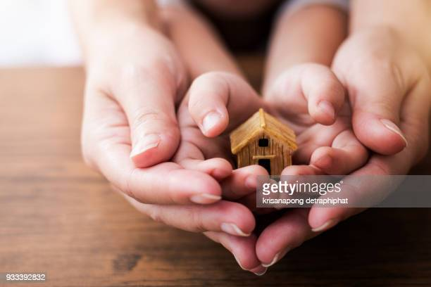 home concept,people, family and home concept - close up of woman and girl holding model house - home insurance stock pictures, royalty-free photos & images