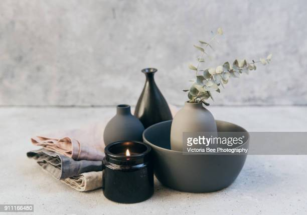 Home decor - neutral coloured vases and dish-ware and linen napkin in nordic style against grey wall.