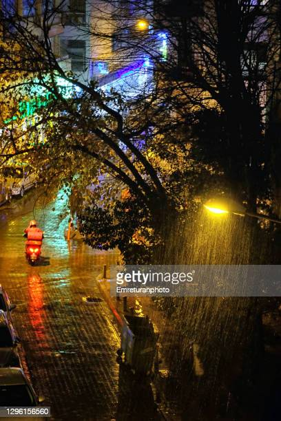 home delivery bike under rain at night. - emreturanphoto stock pictures, royalty-free photos & images