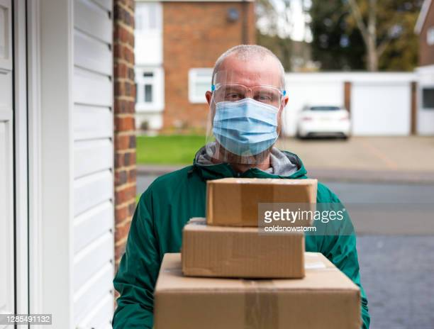 home delivery man with parcels wearing face shield with mask - giving tuesday stock pictures, royalty-free photos & images