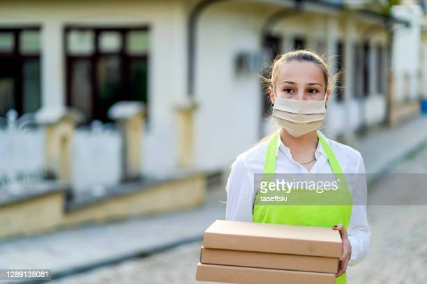 home delivery of a pizza during a pandemic - luggage hold stock pictures, royalty-free photos & images