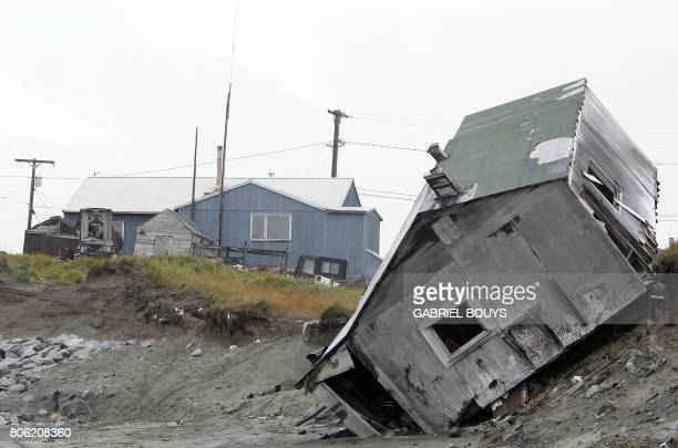 A home destroyed by beach erosion tips over 27 September 2006 in the the Alaskan village of Shishmaref The village home of Inupiat Eskimos is located...