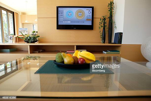 A home energy management system displays power generation and consumption information on a television screen inside a living room of a model smart...