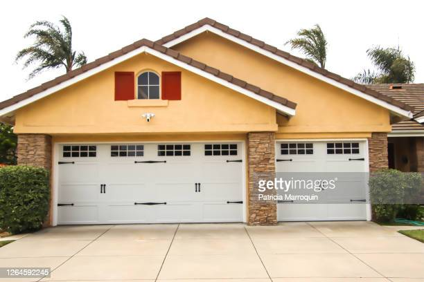 home exterior with carriage style garage doors - driveway stock pictures, royalty-free photos & images