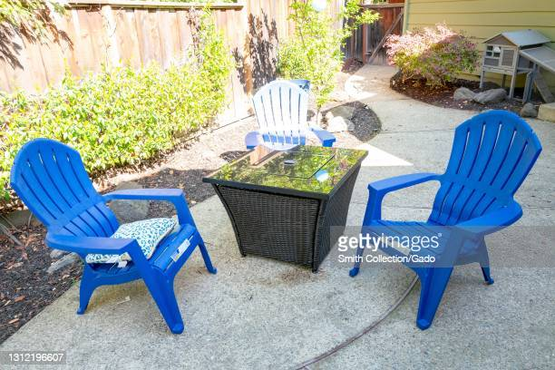 Home firepit and plastic Adirondack chairs providing outdoor seating in a residential backyard, Lafayette, California, April 7, 2021.