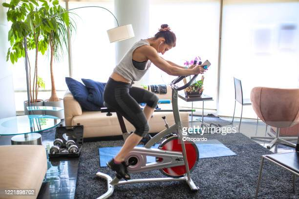 home gym cycing indoors at living room - peloton stock pictures, royalty-free photos & images