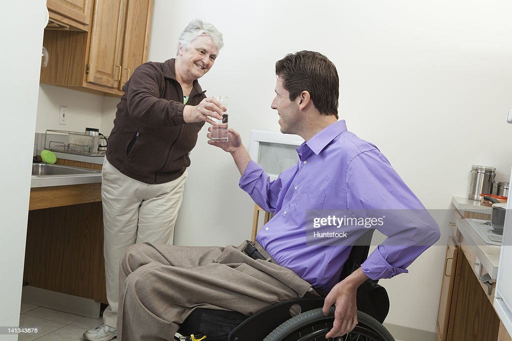 Home health aid offering a glass of water to a man in wheelchair with spinal cord injury : Stock Photo