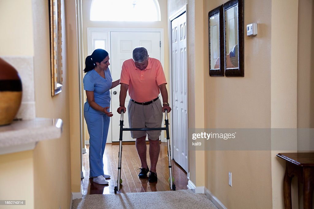 Home health aide with senior man using walker : Stock Photo