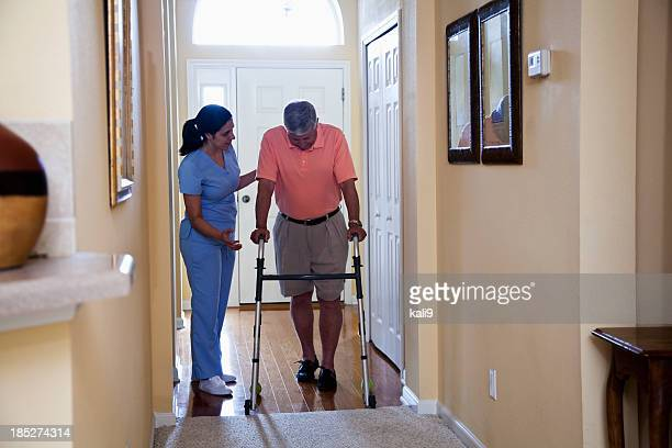 Home health aide with senior man using walker