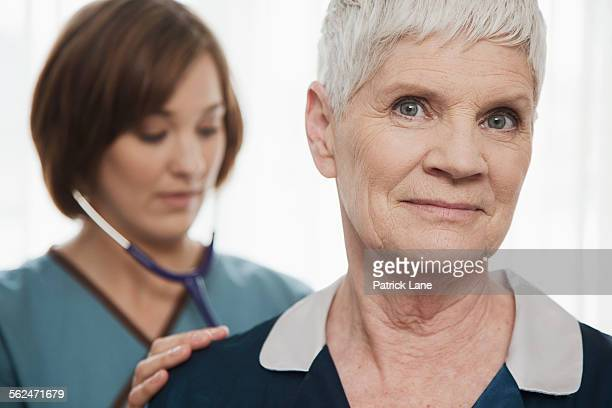 Home health nurse listening to womans breathing