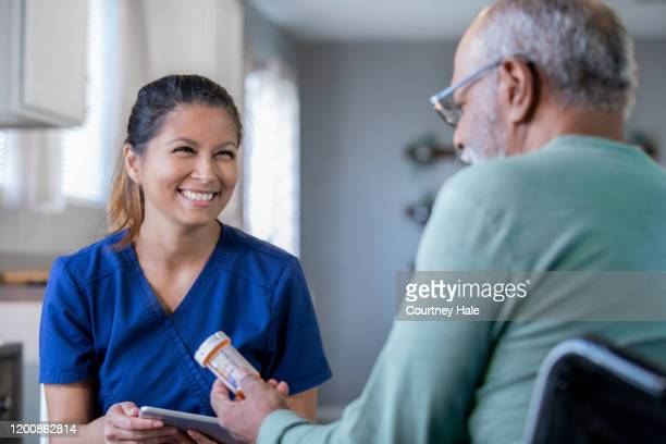 home healthcare nurse brings new prescriptions for senior man - home caregiver stock pictures, royalty-free photos & images