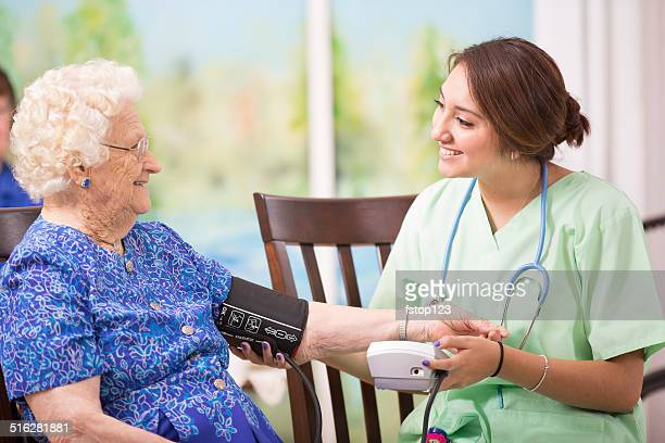 Home healthcare nurse checks blood pressure of elderly woman.